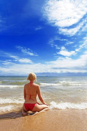 Young woman on the beach looking at horizon