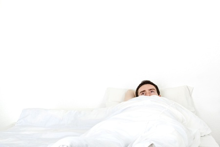Alone young man in a bed under a white blanket