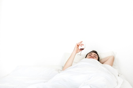 Alone young man in bed dreaming with a glass of wine in hand