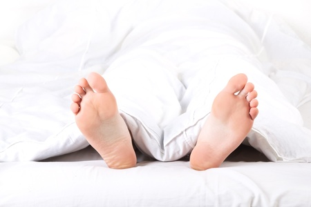 bed feet: Mens feet under a white blanket Stock Photo