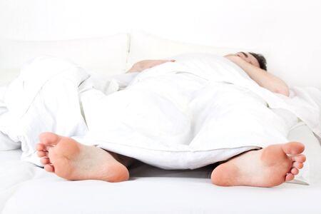piedi nudi ragazzo: Uomo che dorme sotto una coltre bianca Archivio Fotografico