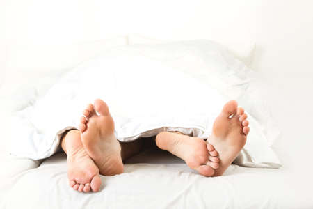 feet naked: Foot of two people in the bedroom, on white background