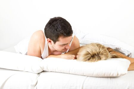Young couple in the bed on white background Stock Photo