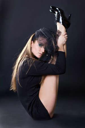 Beautiful flexible young women sitting over dark background Stock Photo