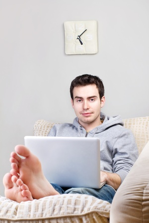 Smiling young man using laptop and lying on the sofa at home