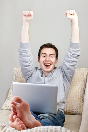 Top view of happy guy sitting on couch and working on laptop