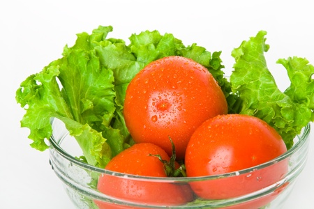 fresh tomato and lettuce in bowl over white