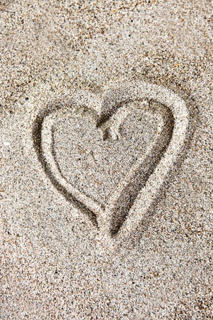 Romantic heart-shaped drawing in the sand