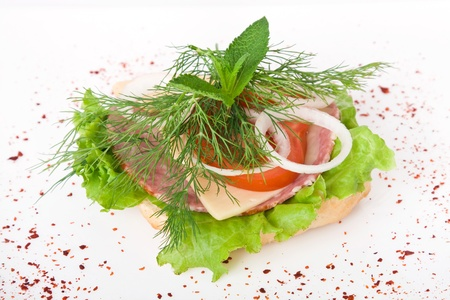Ham, cheese, lettuce, dill and tomato sandwich on a bun. Stock Photo