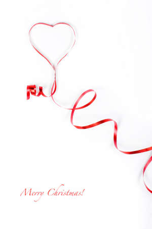 Red ribbon curled in heart shape isolated on white background. Stock Photo