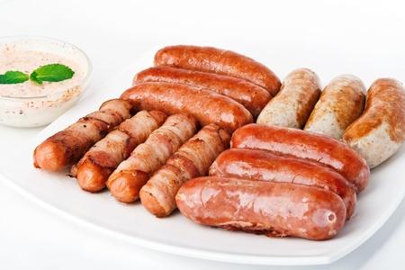 chorizos asados: Salchichas a la parrilla con salsa en plato blanco