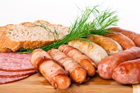 Grilled sausages on a wooden plate with bread and dill Stock Photo