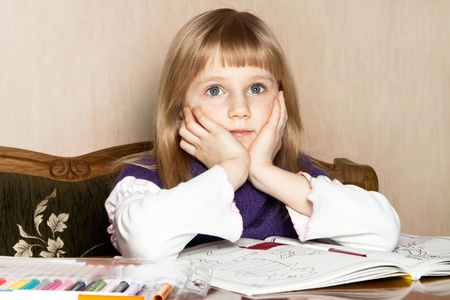 A broody blond girl daydreaming while doing homework