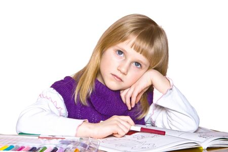 Little girl thinking and drawing in the book, isolated on white photo