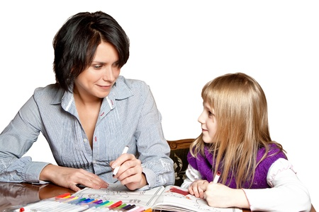 Mother and daughter together is drawing in the book, isolated on white
