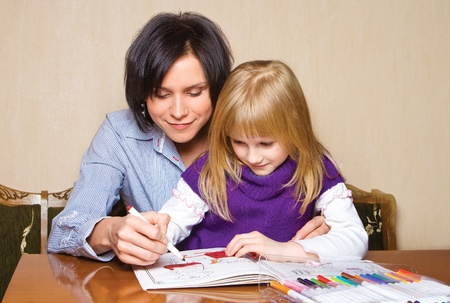 Mother and daughter drawing in the book Stock Photo