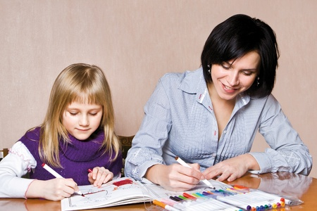 Mother and daughter together is drawing in the book