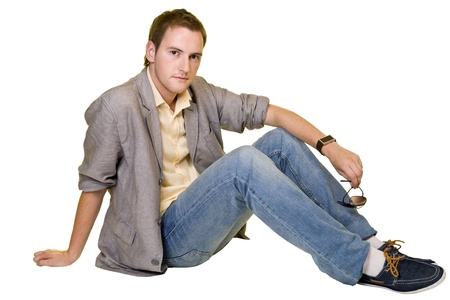 Portrait of a casual young man sitting relaxed. Isolated on white Stock Photo