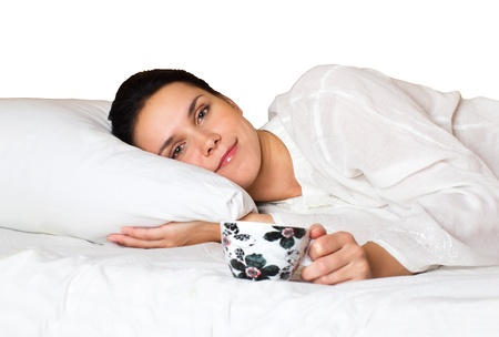 woman lying in bed and tasting coffee