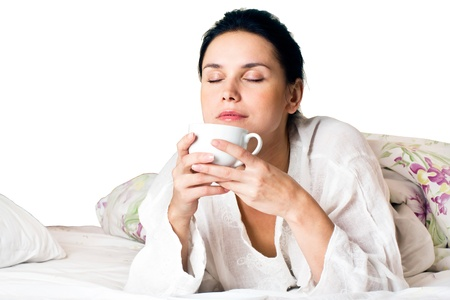 A young woman dreaming and holding white a cup of coffee on bed at bedroom.