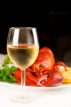 Glass of white wine with cooked lobster on the plate on black background