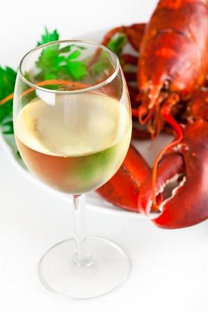 Vaso de vino blanco con langosta cocinada en el plato, vista superior