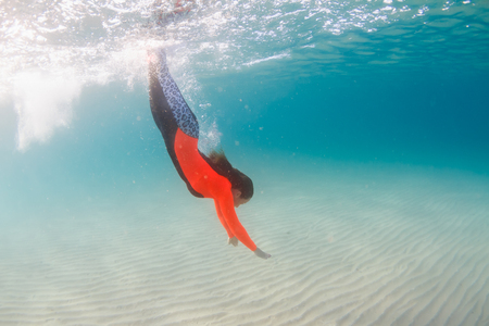 free diving: Woman swimming underwater in the ocean in orange wetsuit Stock Photo