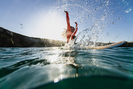 woman sitting on the surfboard in the water and doing splashes
