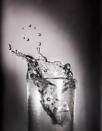 slash: Ice Slash in a Glass of  Water Stock Photo