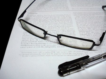 spectacles and pen on paper