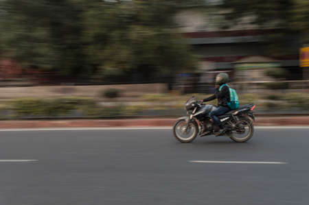 Panning technique of biker who is going for some work at evening on the road