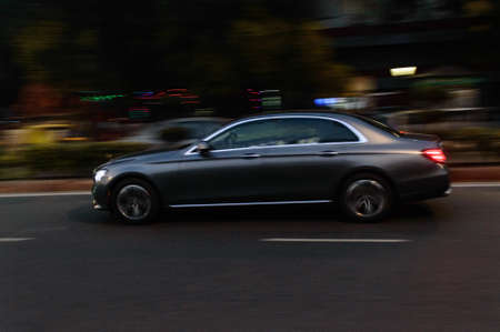 Panning technique of grey car which is going to market at night on the road
