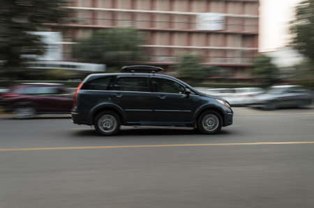 Panning technique of grey car which is going to market at evening on the road