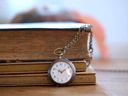 small chain clock in front of some old books