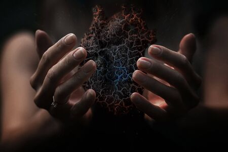 concept burnt charred and freezing realistic heart in beautiful female hands of a girl