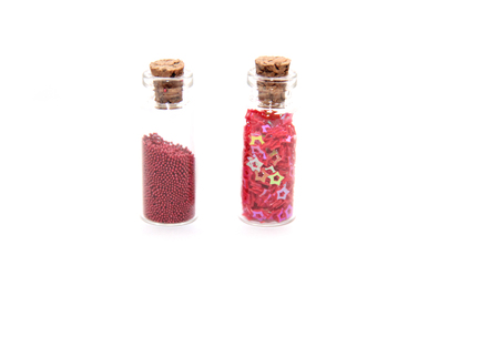 Glitter (small balls and figurines) in small glass bottles with corks