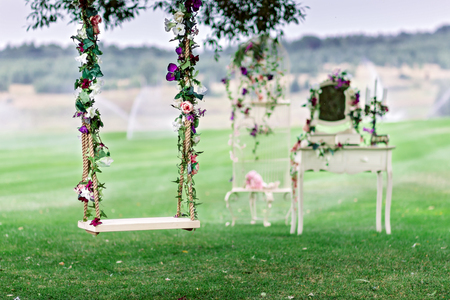 Wedding swing decorated with flowers hanging on the branches of the old willow