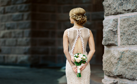 Bride with wedding bouquet, lace dress and beautiful back Standard-Bild