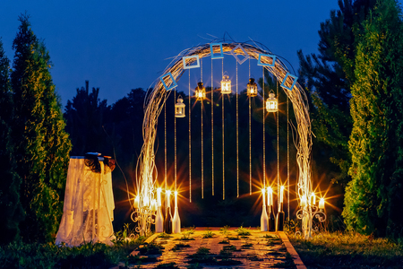 Wedding arch is beautiful at night with candles and lanterns