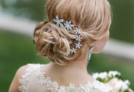 nude bride: Portrait of attractive young woman with beautiful hairstyle and stylish hair accessory, rear view