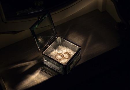 Gold wedding rings in vintage glass jewelry box Foto de archivo
