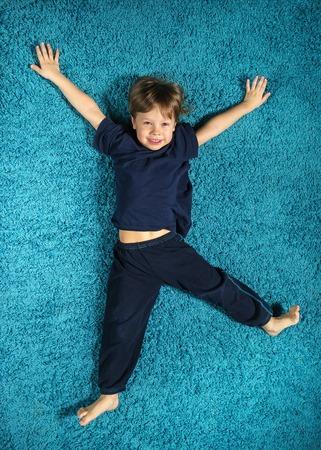 Smiling boy lying on a turquoise carpet Stock Photo