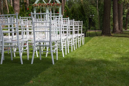 marrying: Classic white wedding chairs on a green lawn, without decoration-2 Summer.