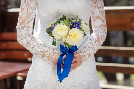 Bride with a bouquet of peonies in hand decorated with blue ribbon
