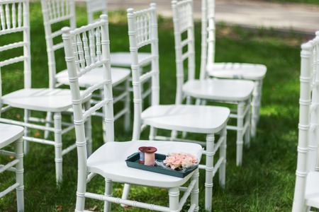 verdant: Chiavari chairs on grass. On one of the chairs lay roses and ribbons