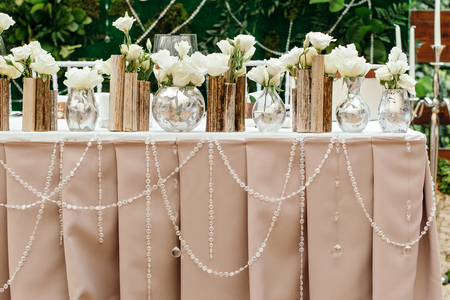 decor: Beautiful decor at the wedding. Flowers standing on the table, adorned with glass garlands Stock Photo
