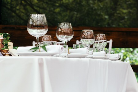 Table for guests on the veranda, white tablecloths and napkins in the background of green Park. Stock Photo