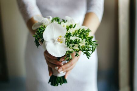 Bride with a bouquet of white Orchid in hand decorated with white ribbon