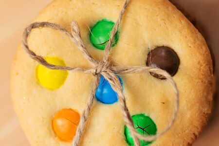 string top: Christmas cookies with colored candies tied string. Top view, close-up. Stock Photo