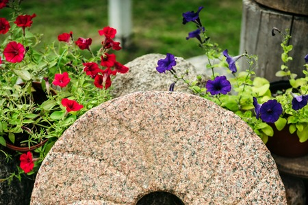 millstone: Old Millstone from the windmill surrounded by flowers. Beautiful rural landscape. Stock Photo